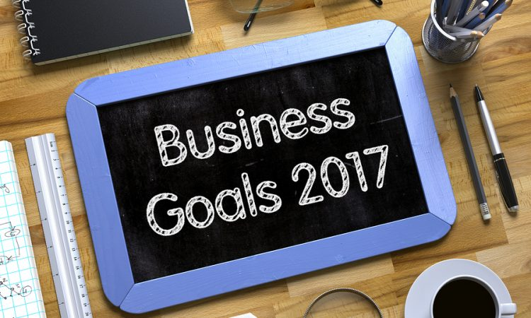EPoS Technology - Business Goals 2017 on Small Chalkboard. Business Goals 2017 Handwritten on Blue Small Chalkboard. Top View of Wooden Office Desk with a Lot of Business and Office Supplies on It. 3d Rendering.